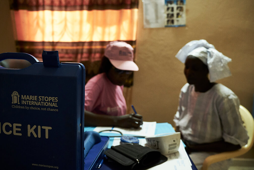 A Senegalese woman in a white head wrap talks to a midwife in a pink hat. Contraception can help reduce maternal mortality.