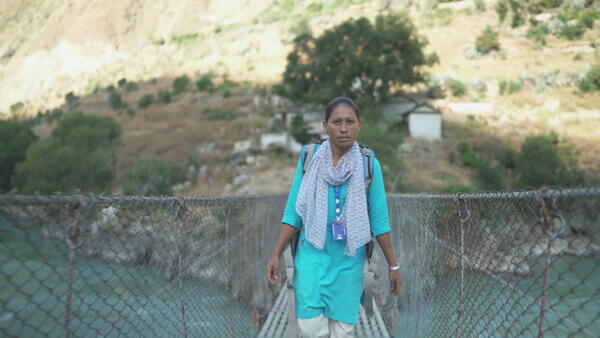 A midwife crosses a bridge in a remote, mountainous area. MSI providers see the consequences of unsafe abortion.