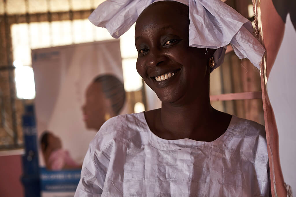 A Senegalese woman in a white head wrap smiles for the camera. In Senegal, maternal mortality remains high, but reproductive healthcare can help.