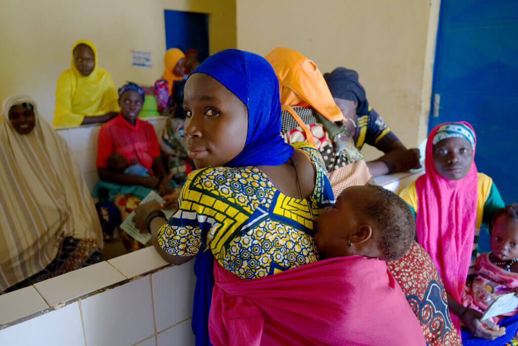 A Black woman in a blue headscarf with a baby on her back stands in a crowded medical clinic.