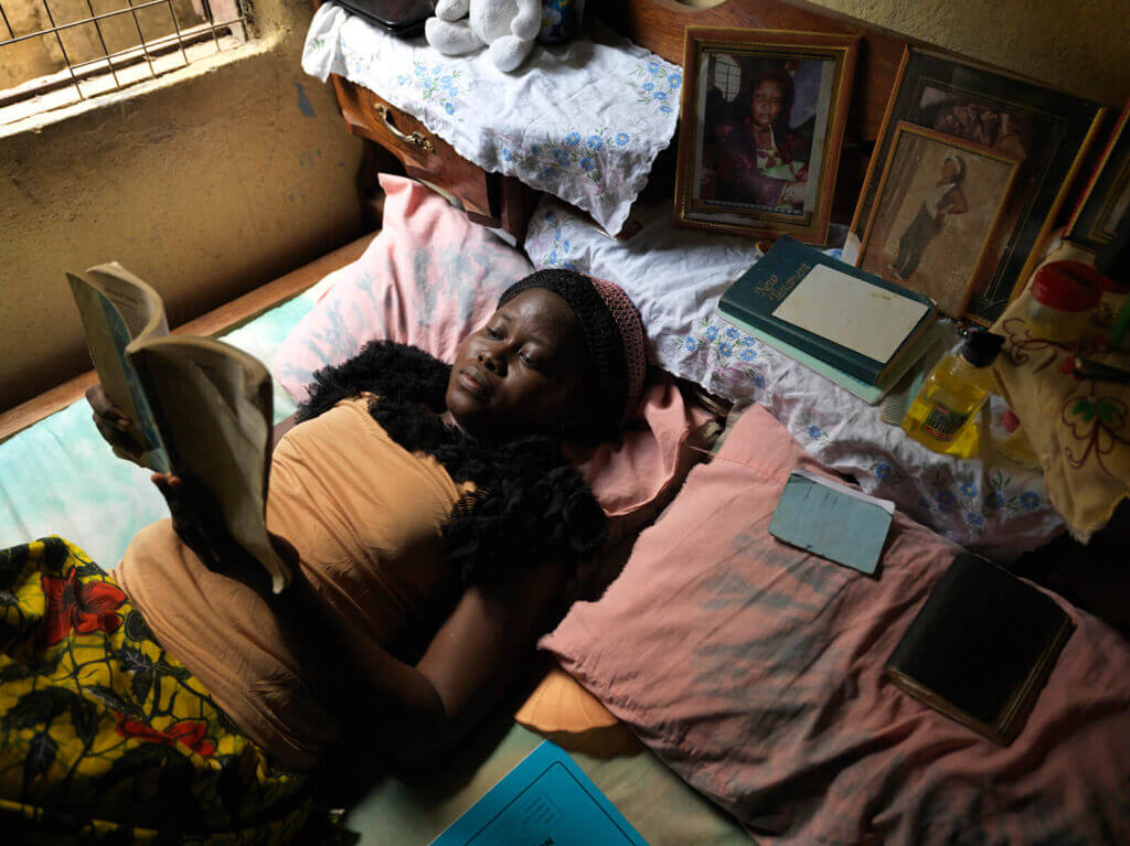 A young woman lays in bed reading a book.