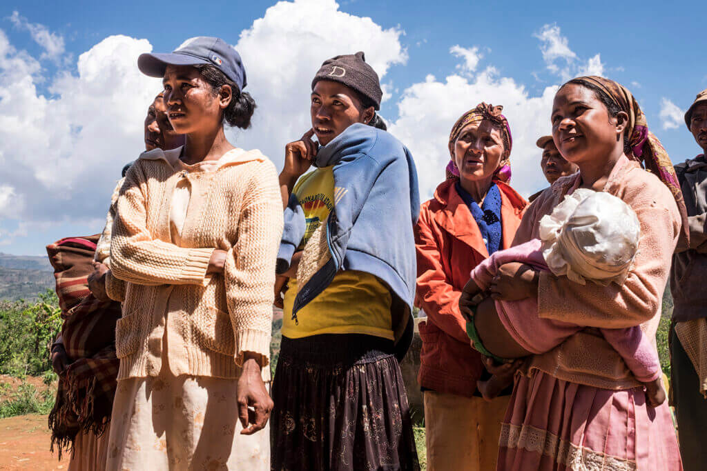 A group of women, some young and some old, stand outside on a sunny day. The landscape behind them is dry.
