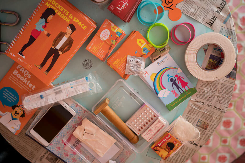 A collection of booklets about sexual health, as well as types of contraception, arranged on a table.