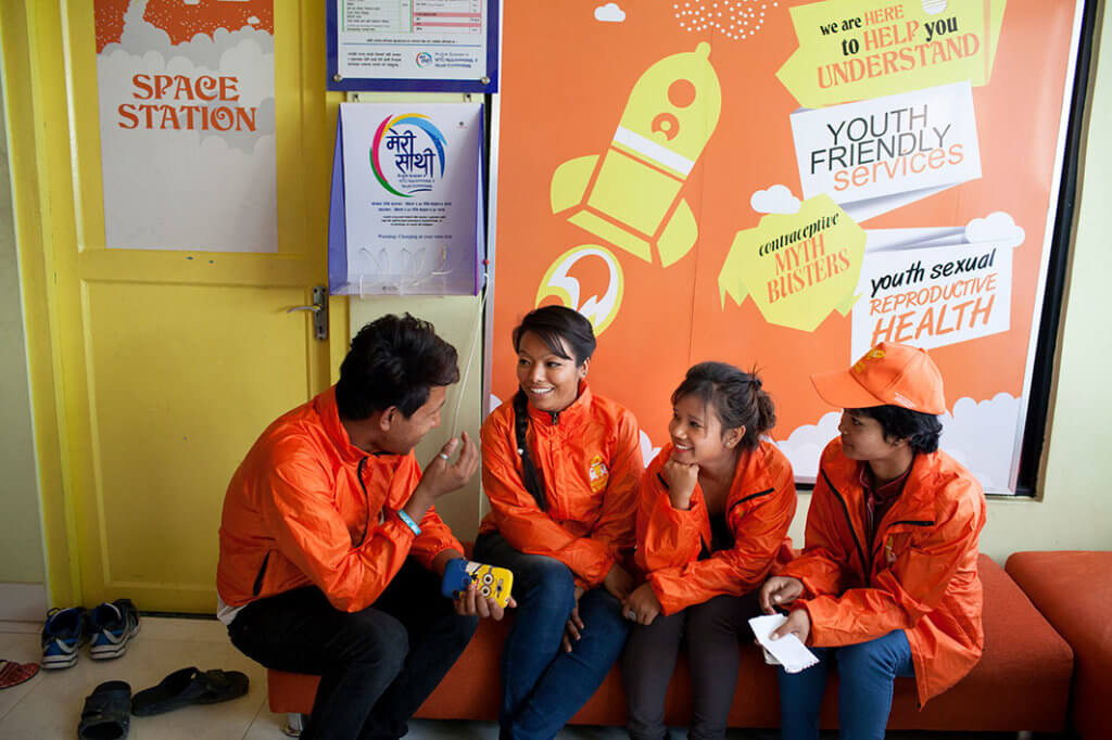 """Four young Nepalese people in orange jackets sit and talk in front of a sign that reads """"Youth sexual reproductive health""""."""