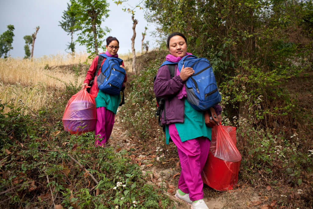 Two nurses carrying medical gear travel down a mountain path. As private providers, they fill the gaps left by Nepal's universal health care system.