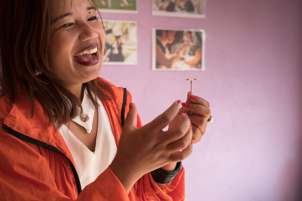 A smiling young woman holds up an IUD at a talk about youth sexual health.