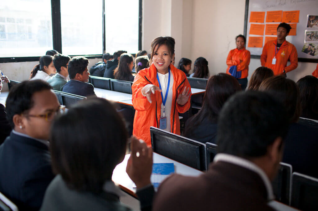 A smiling volunteer in an orange jacket addresses a classroom of young people.