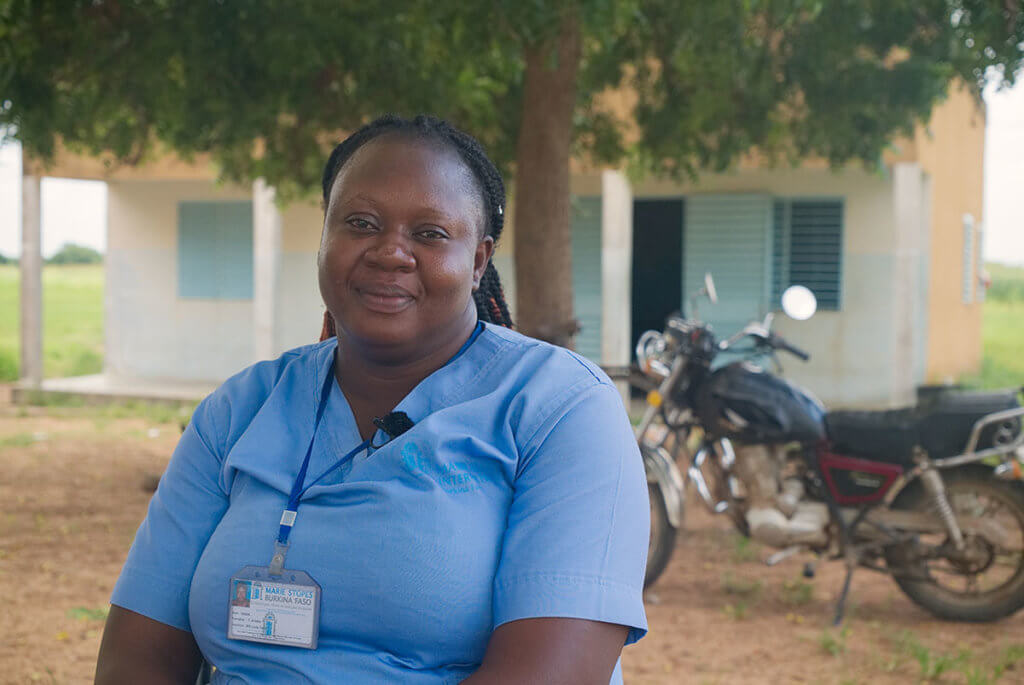 A nurse in a blue t-shirt poses for a photo in a rural setting.