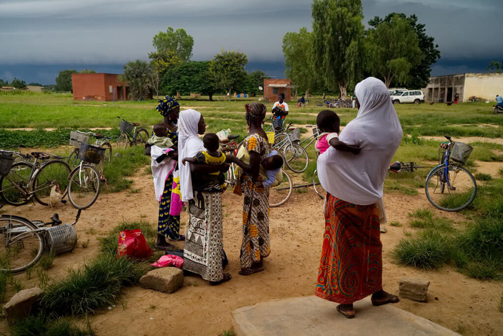 Women in head scarves holding infants outside. Many women in Burkina Faso are internally displaced and in need of reproductive healthcare.