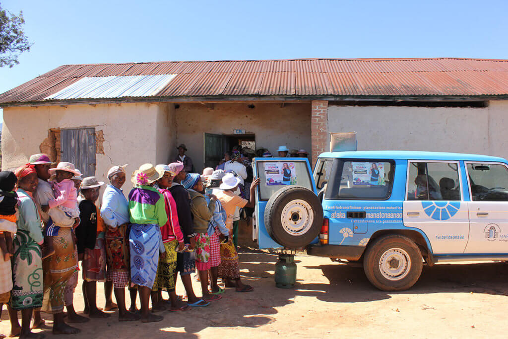 A line of women in colorful scarves and hats wait next to a blue truck in a dry-looking environment. Madagascar is severely impacted by climate change.