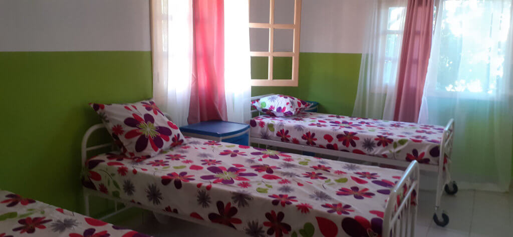 Two beds with floral bedding in a maternity center in Madagascar.
