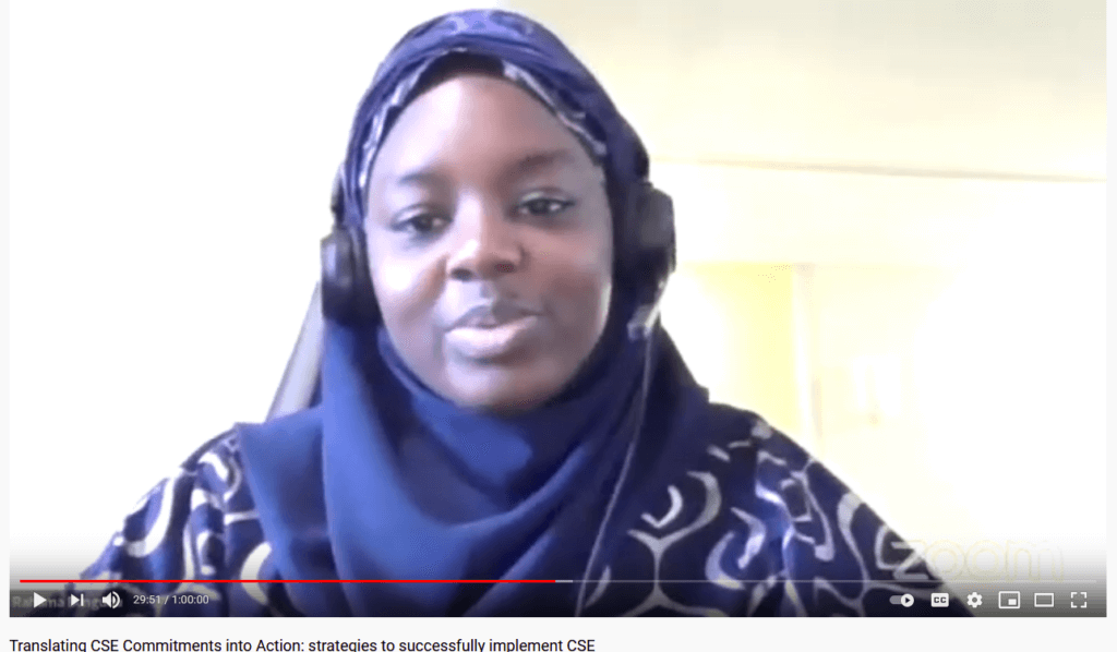 A Nigerian woman in a headscarf and headphones speaks on video about keeping girls in school.